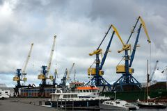 Blue and yellow port cargo cranes in the harbour royalty free stock photography