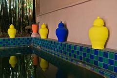 Blue and yellow pots at the edge of tiled fish pond in Majorelle garden Marrakech, Morocco Royalty Free Stock Image