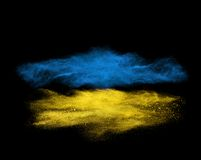 Blue and yellow powder explosion isolated on black royalty free stock photo