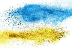 Blue and yellow powder explosion isolated royalty free stock photography