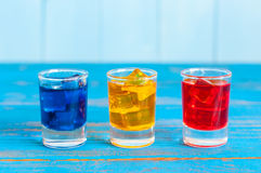 Blue, yellow, rad berry drink or liqueur with ice Stock Photos
