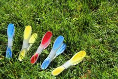 Blue, yellow and red clothes pegs or clothespins on green grass royalty free stock photography
