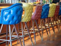 Blue, yellow, and red leather bar chairs lined up in front of bar counter stock photos