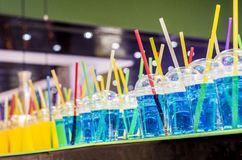 Blue and yellow refreshing drink with tubes. Many glasses with colored water royalty free stock photos