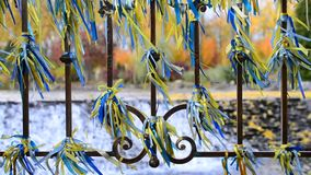 Blue and yellow ribbons tied to an iron fence blown by wind. Beautiful blue and yellow ribbons tied to an iron fence blown by wind on background of scenic stock footage