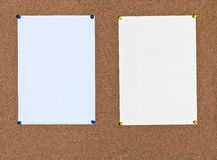 Blue and yellow sheets of paper on cork Royalty Free Stock Image