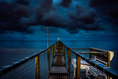Blue and Yellow Steel Framed Dock on Body of Water Under Dark Cloudy Sky Stock Image
