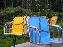 Blue and yellow swings in rain royalty free stock photos