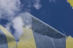 Blue and yellow tattered fabric fluttering in the wind on sky background. Blue and yellow tattered fabric fluttering in the wind on sky background with white Stock Image