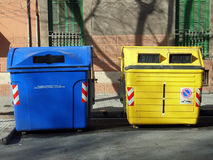 Blue and Yellow wheelie bins. Urban wheelie bins used to separate recyclable materials Royalty Free Stock Photos