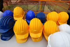 Blue, yellow and white helmets on construction site. Set on a table Stock Images