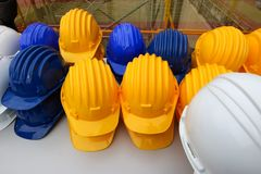 Blue, yellow and white helmets on construction site. Set on a table Stock Image