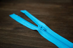 Blue zipper on dark wood background Royalty Free Stock Images