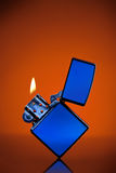 Blue zippo lighter on orange. Blue zippo lighter with flame on orange background Royalty Free Stock Photos