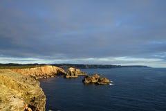 Bluea hav och stenig kust, dramatisk klippa i solnedgångljus royaltyfri fotografi