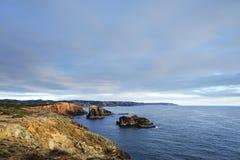 Bluea hav och stenig kust, dramatisk klippa i solnedgångljus royaltyfria foton