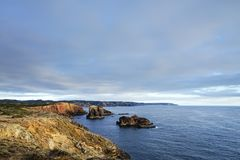 Bluea ocean and rocky coast, dramatic cliff in sunset light Royalty Free Stock Photos