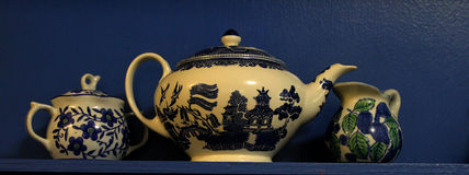 Blue and White China Teapot on a Blue Shelf. A shelf that is painted cobalt blue holds a classic  Old Blue Willow teapot and  blue and white creamer and sugar Royalty Free Stock Image