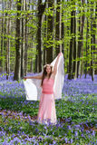 Bluebells fairy. Innocent young woman with pink fairy dress in a springtime bluebells forest Stock Photo