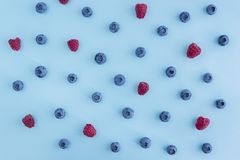Blueberies ans rasperries on blue background, texture. Blueberies and raspberries on blue background, texture, top view Stock Photography