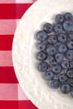 Blueberries. Highbush blueberries on a shiny glazed china plate on a gingham tablecloth Stock Photo