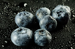 Blueberries on Black. Low key shot of Blueberries isolated on a Black and wet surface royalty free stock photography