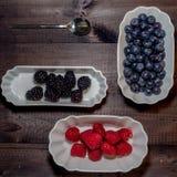 Blueberries, blackberries and raspberries on wooden background stock images