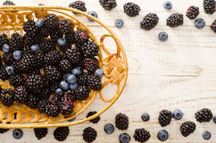 Blueberries and blackberries in a straw basket on a light wooden background. Royalty Free Stock Photo