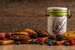 Blueberries, blackberries, strawberries, chocolate biscuits and ceramic jar on wooden table with copy space stock images