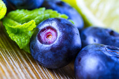Blueberries. Blue blueberries and mint leaves on wooden table Stock Images
