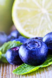 Blueberries. Blue blueberries and mint leaves on wooden table Royalty Free Stock Photo