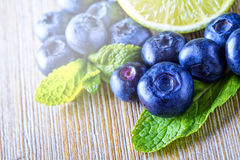 Blueberries. Blue blueberries and mint leaves on wooden table Royalty Free Stock Image