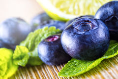 Blueberries. Blue blueberries and mint leaves on wooden table Royalty Free Stock Images