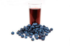 Blueberries And Blueberry Juice. Blueberries are a good source of antioxidants. a clear  glass with berry juice with berries all around on a white background Stock Photo