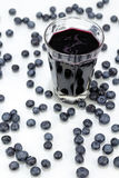 Blueberries and Blueberry Juice. Deep purple berry juice in clear glass, whole fruit abstract on white reflective surface Stock Photo