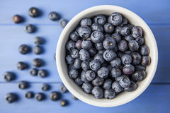 Blueberries in bowl on blue background. Fresh blueberries on blue background Royalty Free Stock Photos