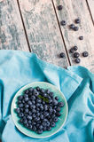 Blueberries in a bowl. Blue tone. Berries in a bowl on the blue tablecloth and old wood. Summer composition Royalty Free Stock Photo