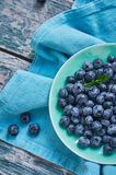 Blueberries in a bowl. Blue tone. Berries in a bowl on the blue tablecloth and old wood. Summer composition Stock Photography