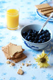 Blueberries in a bowl, breakfast scene on rustic wooden background. Blueberries in a bowl, biscuits and orange juice, fresh breakfast scene on rustic wooden Stock Photography