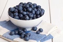 Blueberries in bowl. Fresh organic blueberries in white bowl on white wooden kitchen table Royalty Free Stock Image