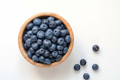 Blueberries in bowl over white background. Blueberries in wooden bowl isolated on white background. Top view and copy space Stock Photography