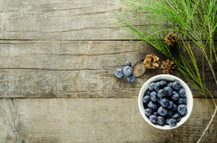 Blueberries. On bowl with pine cones and pine leaves on a rough textured wood Stock Photo