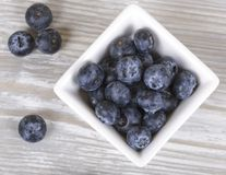 Blueberries in a bowl top view. Blueberry in the Cup on a gray background, fresh berries, dietary food Stock Images