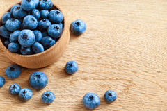 Blueberries in bowl on wooden table. Stock Photos
