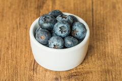 Blueberries in a bowl on a wooden table Royalty Free Stock Images