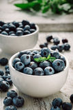 Blueberries in bowls. Close-up of blueberries in two bowls standing on a  wooden table Stock Photo