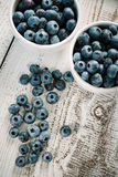Blueberries in bowls. Close-up of blueberries in two bowls standing on a wooden table Stock Image