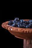 Blueberries in brown cup. View from above on handful of ripe and fresh blueberries in brown wooden cup and some blueberries sprinkled on white wooden desk Stock Image