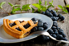 Blueberries cake on dish. With fork over wood table Stock Images