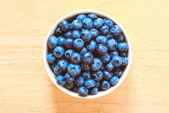 Blueberries in the ceramic bowl on the wood Royalty Free Stock Photography